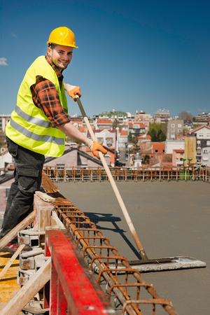concreting: Construction worker smoothing concrete on a roof