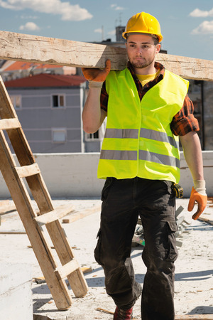 carrying: Construction worker carrying wooden beams Stock Photo