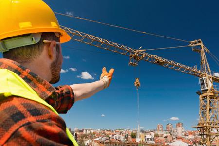 signaling: Construction worker signaling to crane operator Stock Photo