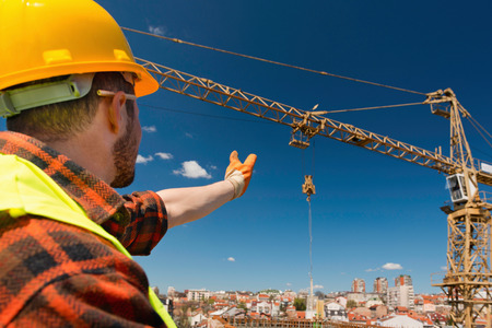 Construction worker signaling to crane operator Banque d'images