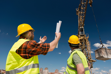 signaling: Construction workers signaling to crane operator