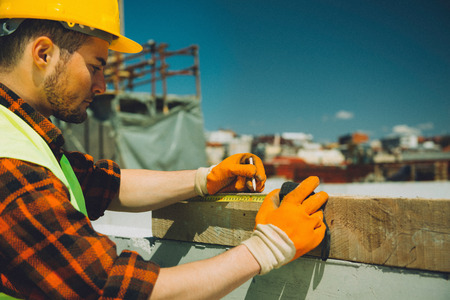 work gloves: Construction worker on site, measuring wooden beam. Toned image, fine grain added