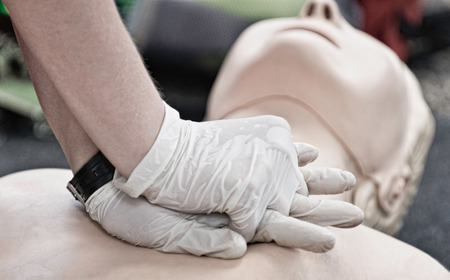 compressions: CPR - Demonstrating chest compressions on CPR dummy