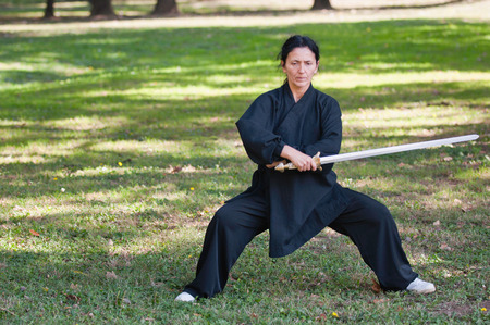 full strenght: Martial arts master with sword in a fighting stance