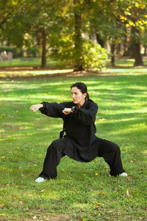combative sport: Woman doing Tai Chi on field Stock Photo