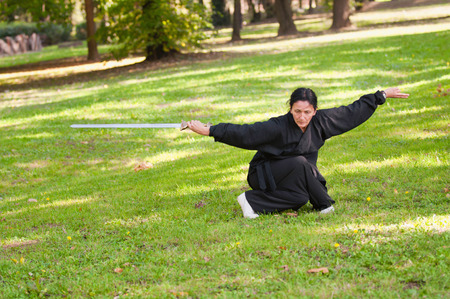 fighting stance: Kung Fu Sword practitioner in fighting stance. Stock Photo