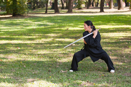 full strenght: Martial arts sword master practicing in nature