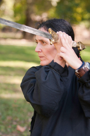 fighting stance: Female martial arts master with sword in defensive fighting stance