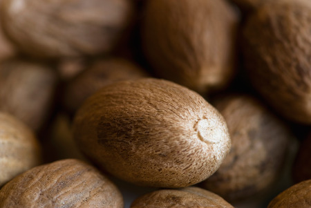 Nutmeg background with central nut in focus Stock Photo