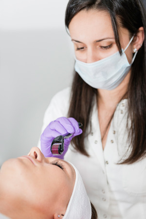 Dermatologist using dermal roller for skin treatment