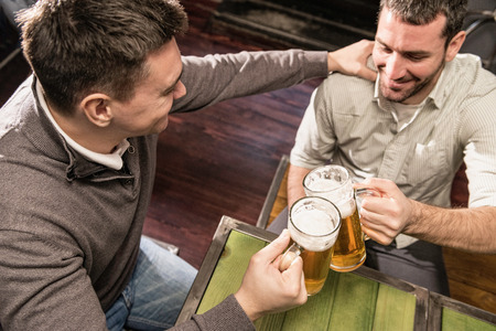beer after work: Good friends in pub, toasting with beer Stock Photo