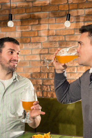 drinks after work: Friends drinking beer in bar Stock Photo