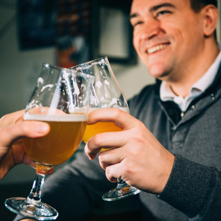 toned image: Friends toasting with beer, positive atmosphere. Toned image, focus on glasses