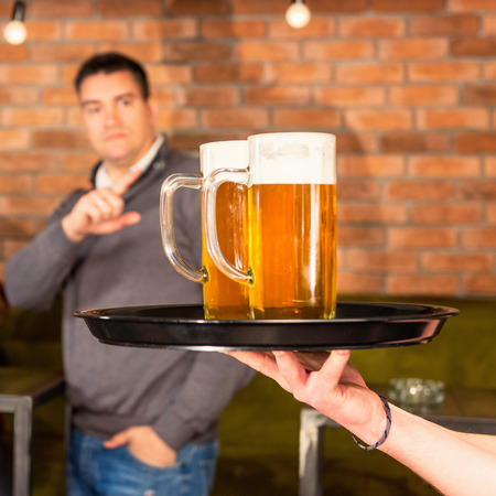 ordering: Ordering beer in pub. Focus on mugs, blurred background