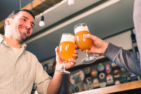 drinks after work: Positive smiling friends drinking beer, having fun in bar