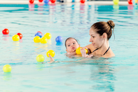 6 12 months: Baby boy with mother, swimming pool