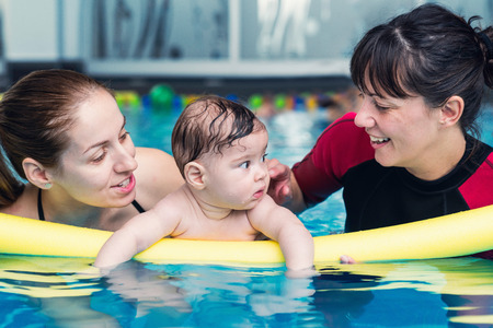 6 12 months: Swimming for babies - little baby boy in swimming pool with his mother and instructor
