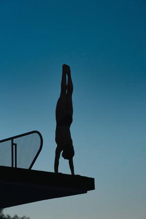 Silhouette de plongeur en poirier, se préparant à plonger de la plate-forme. Photographié au crépuscule Banque d'images