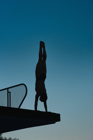 Silhouette of diver in handstand, preparing to dive from platform. Photographed at dusk