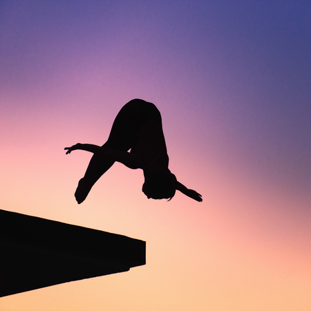 somersault: Silhouette of lady diver, diving from platform. Photographed at dusk against setting sun, colorful sky as background