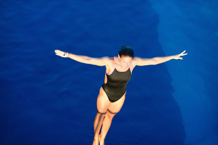 Female diver on platform, preparing to dive, view from above Stok Fotoğraf