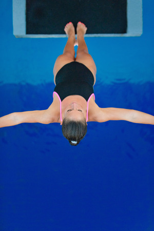 unusual angle: Female diver on platform, preparing for back dive. Photographed from unusual angle, directly above