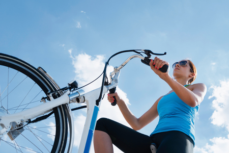 Riding electric bicycle or e-bike, shot against blue sky, convenient copy space