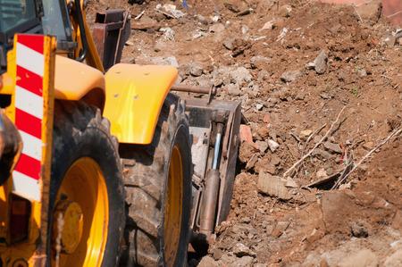 cargador frontal: pala cargadora limpiar la suciedad en el sitio de construcci�n. enfoque selectivo