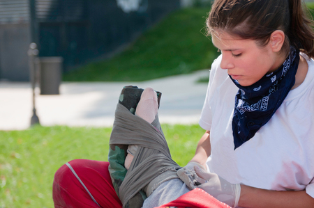 paramedic: Paramedic bandaging ankle on the CPR dummy