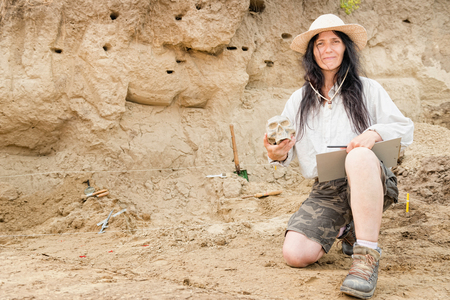 archaeologist: Archaeologist proudly presenting discovery at archaeological site