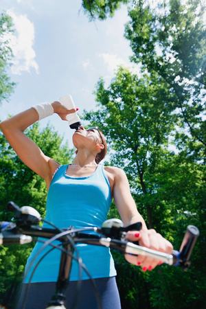 taking a break: Girl taking a break after bicycle ride through the forest Stock Photo