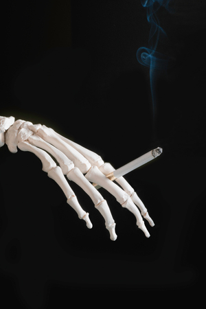 decease: Skeleton hand holding burning cigarette on black background