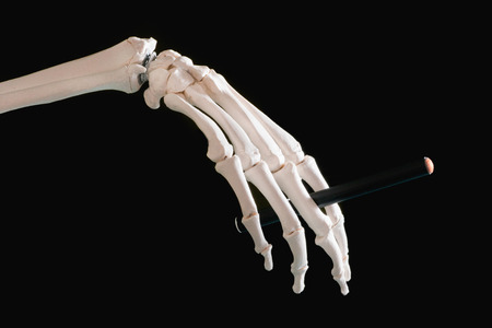 hand up: Skeleton hand holding electronic cigarette