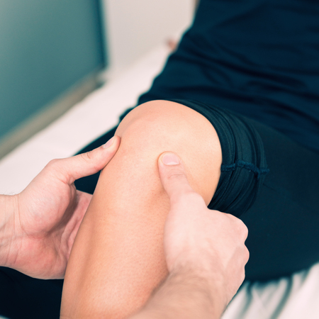 examining: Physical therapist examining patients knee