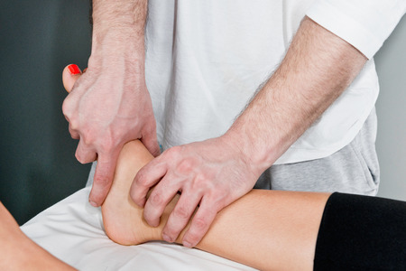 osteopath: Osteopath working on patients ankle