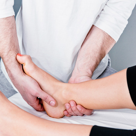 Swollen: Osteopath working with swollen ankle, close-up Stock Photo