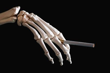 anti smoking: Skeleton hand holding cigarette Stock Photo