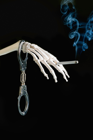 fag: Deadly smoking addiction - Concept with skeleton hand with burning cigarette and handcuffs