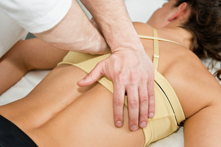 Chiropractor treating patients back, etiopathy