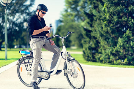 electric cell: Businessman on electric bicycle using cell phone