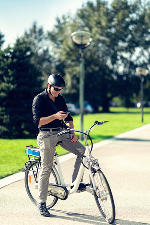 electric cell: Businessman on electric bicycle typing on cell phone