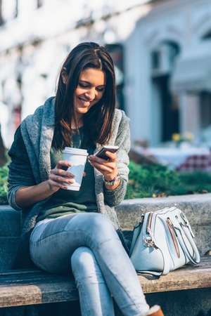 20 29: Teenager with take-away coffee in the city sitting and using mobile phone. Texting with friends and drinking coffee fron cup.