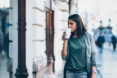 women holding cup: Girl with a take-away coffe in the city looking storesand shopping