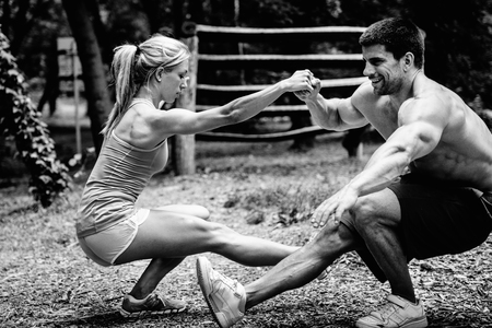 Crossfit couple doing pistol squats in park Stock Photo