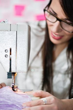 20 24: Fashion designer sewing on sewing machine Stock Photo