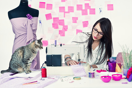 20   24: Fashion designer working with sewing machine and curious cat