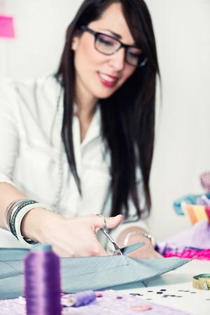 textile designer: Fashion designer cutting textile