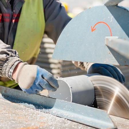 circular saw: Construction worker cutting plastic pipe on a circular saw