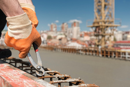 tightening: Tightening concrete armature wire mesh with pliers Stock Photo