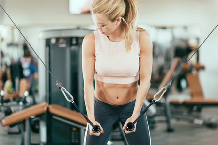 Female athlete exercising on cable crossover fitness machine in the gym Stock Photo